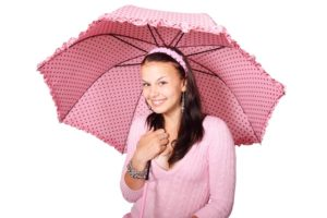 Young woman wearing pink holding a pink umbrella
